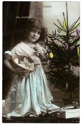 AVQ-A-002062-0011 - Portrait of a young little girl while eating a cookie and carrying a basket under the Christmas tree, Christmas greeting post-card, with a 'Buon Natale' inscription on the front side and a personal dedication on the back side, the postage stamp indicates the date of 24th of December 1914, Peschiera, Verona, Italy
