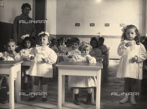 "AVQ-A-002890-0002 - ""Inauguration of the Nursery School named after Prof. Giovanni Calò"" in Bologna. A few posing schoolchildren sitting a classroom"