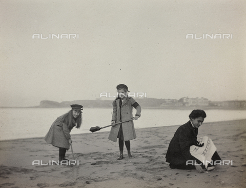 "AVQ-A-004516-0414 - Album "" Route photo of an American family from the United States (New Jersey) in Florence, 1899-1912 "": Harriet and Anita Self with the nurse while playing on the beach of St Jean De Luz"