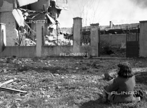 Ail-f-158393-0000 - World War II: Anglo-American bombing of 28/03/1944. A little girl next to the rubble of a bombarded building, Mestre - Data dello scatto: 28/03/1944 - Luce Institute/Alinari Archives Management, Florence