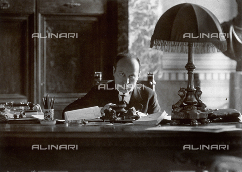 BAA-F-000033-0000 - Portrait of Benito Mussolini sitting at his writing-desk in his studio. In the foreground a lamp, book, papers and various stationery objects are visible - Date of photography: 1930 ca. - Fratelli Alinari Museum Collections-Badodi Archive, Florence