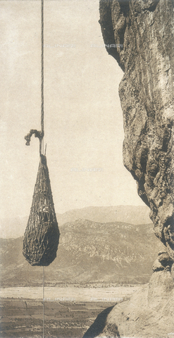 "BAF-A-004894-0093 - ""En Grèce par monts et par vaux"" (""In Greece Through Mountains and Valleys""): Tourist raised with a net to reach the Holy Trinity Monastery, on the peak of Meteora - Data dello scatto: 1903-1910 - Archivi Alinari, Firenze"