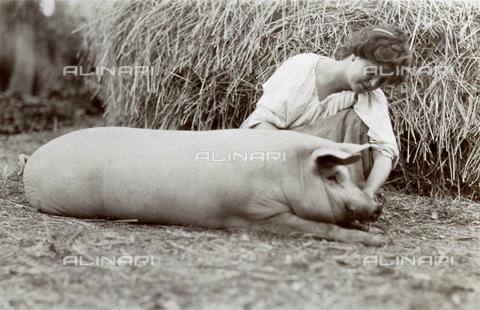 BAQ-F-001139-0000 - Giovane contadina inginocchiata accanto a un piccolo suino. - Data dello scatto: 1907 - 1913 ca. - Raccolte Museali Fratelli Alinari (RMFA), Firenze