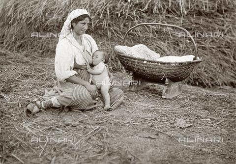 BAQ-F-001153-0000 - Giovane contadina allatta il proprio bambino seduta per terra in un fienile. - Data dello scatto: 1907 - 1913 ca. - Raccolte Museali Fratelli Alinari (RMFA), Firenze