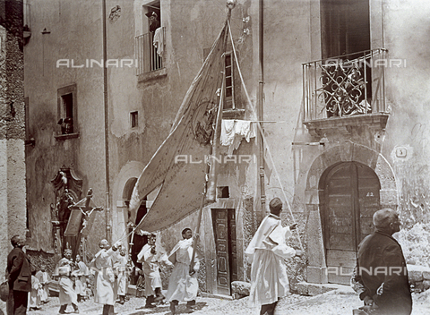 BAQ-F-001323-0000 - Processione della Madonna del Carmine a Scanno: un gruppo di laici in vesti bianche procede lungo la via con un alto stendardo ed un crocifisso - Data dello scatto: 16/07/1910 - Raccolte Museali Fratelli Alinari (RMFA), Firenze