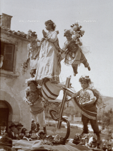 """BAQ-F-001356-0000 - """"Living picture"""" carried on a procession along the road in a small town. A young woman disguised as the Blessed Virgin Mary is lifted from the ground, her feet laying on the terrestrial globe and on the moon. - Data dello scatto: 1900 ca - Archivi Alinari, Firenze"""