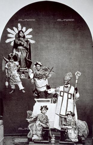 """BAQ-F-001388-0000 - """"Tableaux vivants"""" : La complicata composizione plastica mostra un uomo, nelle vesti di un vescovo, con il pastorale in mano, davanti ad un altare. In primo piano due bimbe vestite da angeli posano inginocchiate al cospettodel prelato. In alto a sinistra, sospesa in aria, una fanciulla impersona una santa ascesa al cielo, attorniata da due angioletti aventi in mano un crocifisso ed un turibolo. - Data dello scatto: 1874 ca. - Raccolte Museali Fratelli Alinari (RMFA), Firenze"""