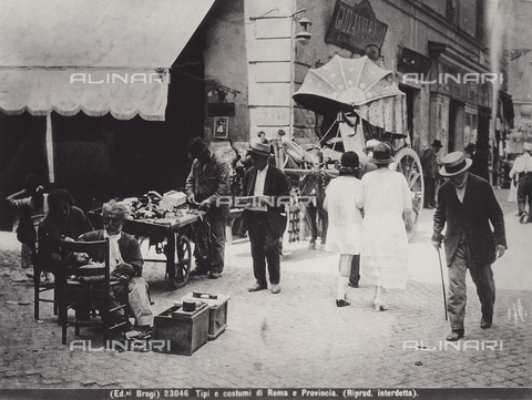 BGA-F-023046-0000 - Men and women walking along a street of Rome with some work benches and a parked coach.