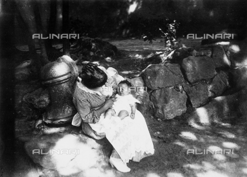 BGA-F-023050-0000 - A mother feeding her son sitting on a rock along a road in the environs of Rome.