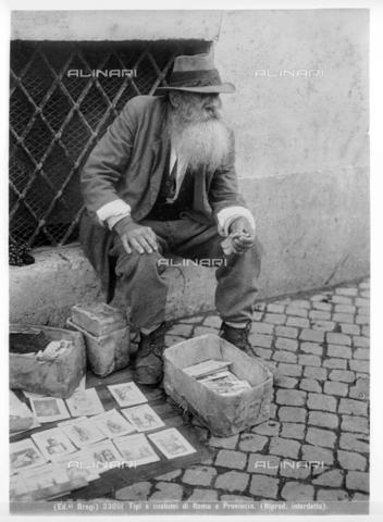 BGA-F-023051-0000 - An old man sitting on a short wall of a grated window in Rome, is selling old books of operas and comedies.