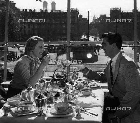 BPK-S-AA3000-4189 - A couple of American tourists while having breakfast in a hotel in Munich - Data dello scatto: 1952 - Hanns Hubmann / BPK/Alinari Archives