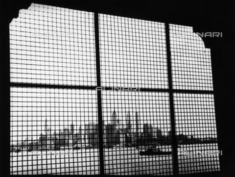 BPK-S-AA3001-9871 - View from the metali grill of a window at Ellis Island of the skyscrapers in Manhattan, New York - Data dello scatto: 1932 - Erich Salomon / BPK/Alinari Archives