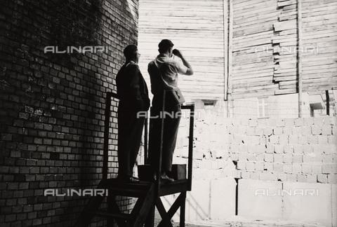 BPK-S-AA3002-6400 - Muro di Berlino: padre e figlio guardano attraverso una fessura del muro - Data dello scatto: 1963 - BPK/Archivi Alinari, Kunstbibliothek, SMB / Bernard Larsson