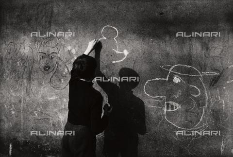 BPK-S-AA3002-6453 - Muro di Berlino: un ragazzo disegna Topolino sul muro - Data dello scatto: 1963 - BPK/Archivi Alinari, Kunstbibliothek, SMB / Bernard Larsson