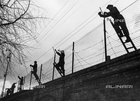 BPK-S-AA3003-6895 - Muro di Berlino: soldati sistemano il filo spinato lungo i binari della S-Bahn nella stazione nord di Berlino Est, situata direttamente sul muro, per evitare tentativi di fuga - Data dello scatto: 1961-1965 ca. - BPK/Archivi Alinari, Klaus Lehnartz