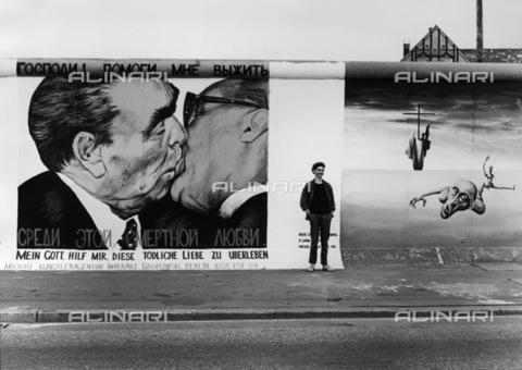 """BPK-S-AA3003-7396 - Muro di Berlino: murales raffigurante il bacio fraterno tra Leonid Brezhnev e Erich Honecker. In basso la scritta """"Mio Dio, aiutami a sopravvivere a questo amore mortale"""" - Data dello scatto: 16/06/1990 - BPK/Archivi Alinari, Manfred Uhlenhut"""