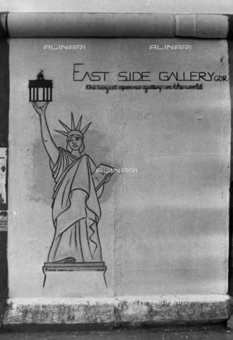 """BPK-S-AA3004-4082 - Muro di Berlino: """"East Side Gallery GDR - the largest open-air gallery of the world"""" murale raffigurante la statua della Libertà realizzato da David Monty - Data dello scatto: 1990 - BPK/Archivi Alinari, Helmut Schà¤fer"""