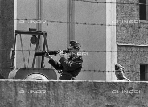BPK-S-AA7013-6219 - Berlin Wall: GDR soldier photographed in a control post on the wall - Klaus Lehnartz / BPK/Alinari Archives
