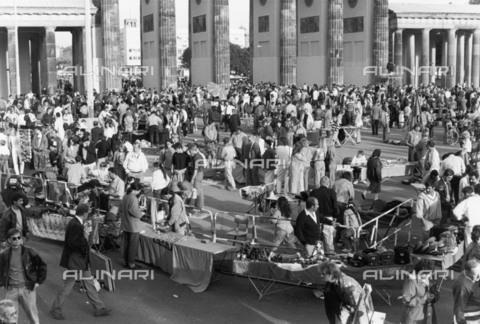 BPK-S-AA7014-3245 - Fall of the Berlin Wall: parts of the wall, equipment of Soviet soldiers and other souvenirs for sale in front of the Brandenburg Gate - Data dello scatto: 02/10/1990 - Dietmar Katz / BPK/Alinari Archives