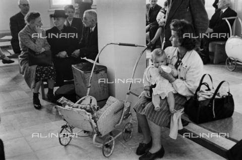 BPK-S-AA7015-5427 - Una madre allatta un neonato nella sala d'attesa del consolato generale degli Stati Uniti in Ludwigstraße, Monaco - Data dello scatto: 10/1947 - Hanns Hubmann / BPK/Archivi Alinari