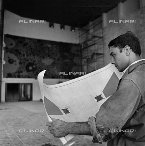 BPK-S-AA7015-6827 - L'artista francese Yves Klein (1928-1962) ritratto mentre legge un giornale davanti alla sua opera d'arte realizzata per Teatro Comunale di Gelsenkirchen in Germania - Data dello scatto: 1958 - Charles Wilp / BPK/Archivi Alinari