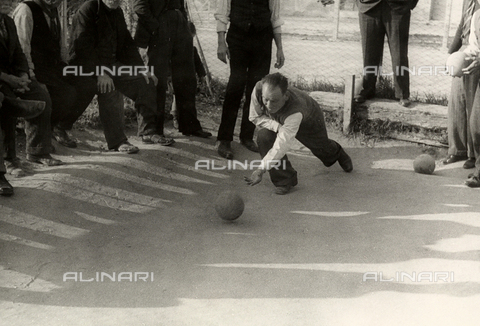 """BVA-F-000209-0000 - """"The game of bocce"""". A bocce player photograph at the moment of releasing a ball. Around him, other players are visible."""
