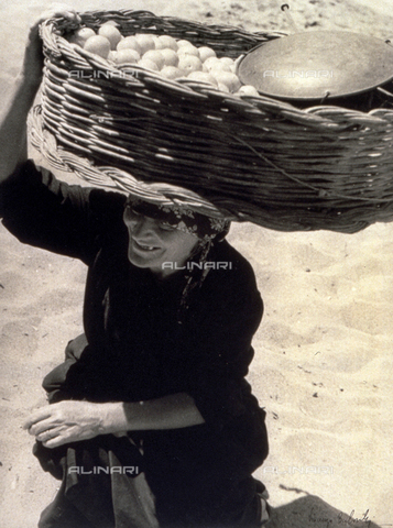 BVA-F-001187-0000 - Elderly woman carrying a large basket full of apples on her head - Date of photography: 1938 ca. - Alinari Archives-Balocchi archive, Florence
