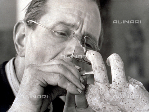 BVA-F-001194-0000 - Close-up of a restorer cleaning the hand of a wooden sculpture - Date of photography: 1949 ca. - Alinari Archives-Balocchi archive, Florence