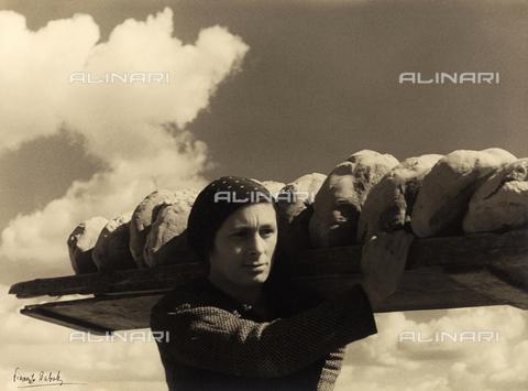 BVA-F-001282-0000 - Giovane donna trasporta numerose forme di pane, disposte su di un'asse, appoggiata sulla spalla - Data dello scatto: 1939 ca. - Archivi Alinari, Firenze