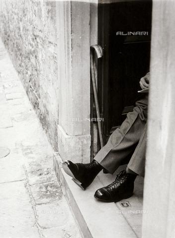 BVA-F-001665-0000 - Le gambe di un uomo spuntano dal portone di una casa - Data dello scatto: 1960 ca. - Archivi Alinari, Firenze