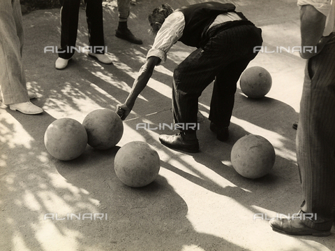 """BVA-F-002415-0000 - """"Game of bocce"""". A player measuring the distance between two bocce balls. Around him, other players watch the scene."""