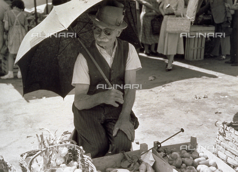 BVA-F-003747-0000 - Old peasant selling vegetables at the market, protecting himself from the sun with an umbrella - Date of photography: 1950 ca. - Alinari Archives-Balocchi archive, Florence