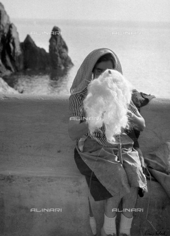 BVA-F-003753-0000 - Portrait of an elederly peasant spinning wool. In the background yhe sea - Date of photography: 1950 ca. - Alinari Archives-Balocchi archive, Florence