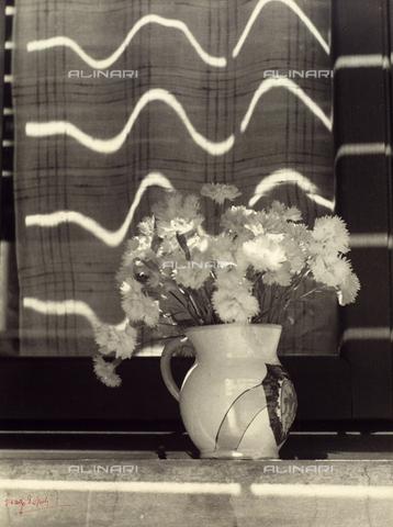 """BVA-F-003812-0000 - """"Il vaso di garofani"""". Primo piano su un vaso con garofani, collocato sul davanzale di una finestra. La luce del sole è riflessa sui vetri delle imposte, creando un effetto ondulatorio."""