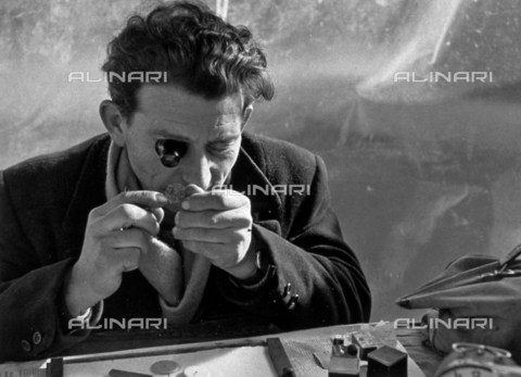 BVA-F-006068-0000 - Half-length portrait of a man looking at small objects with a monocle lens - Date of photography: 1950 -1960 ca. - Alinari Archives-Balocchi archive, Florence