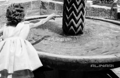 BVA-S-S10010-0011 - Little girl photographed in front of the fountain of King William II in the cloister of the Cathedral of Monreale - Date of photography: 1960-1961 - Fratelli Alinari Museum Collections-Balocchi Archive, Florence