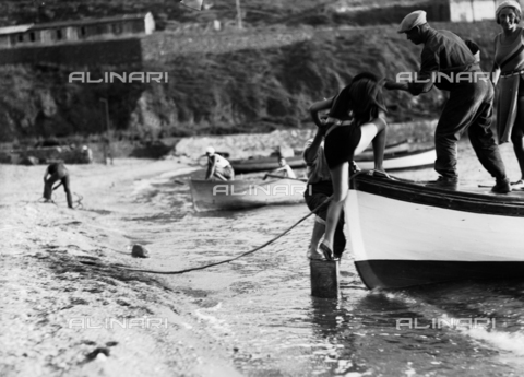 CAD-S-030005-0004 - Woman being helped to get on a boat by the sea - Date of photography: 1925-1930 - Fratelli Alinari Museum Collections-Cammarata Donation, Florence