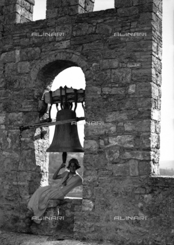 CAD-S-080001-0001 - Portrait of a young woman near the bell of the Rocca di Staggia Senese castle - Date of photography: 14/09/1924 - Fratelli Alinari Museum Collections-Cammarata Donation, Florence