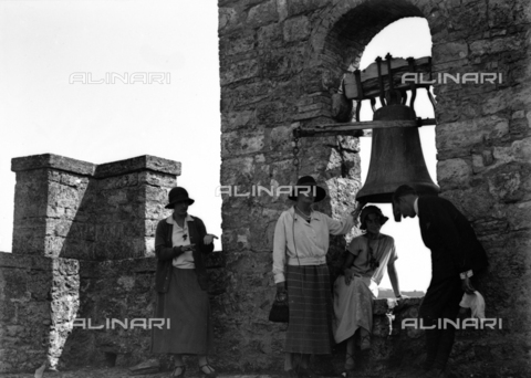 CAD-S-080001-0002 - Portrait of a young woman near the bell of the Rocca di Staggia Senese castle - Date of photography: 14/09/1924 - Fratelli Alinari Museum Collections-Cammarata Donation, Florence