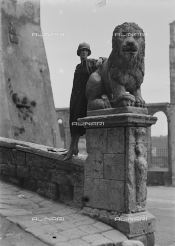 CAD-S-120001-0010 - Portrait of a woman near of a stone lion in Pitigliano - Date of photography: 11-13/04/1925 - Alinari Archives-Monteverde archive, Florence