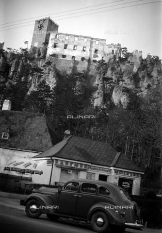 CAD-S-290047-0009 - Veduta di rovine di castello vicino a strada con automobile parcheggiata vicino ad un caffè - Data dello scatto: 1930 ca - Raccolte Museali Fratelli Alinari (RMFA)-donazione Cammarata, Firenze