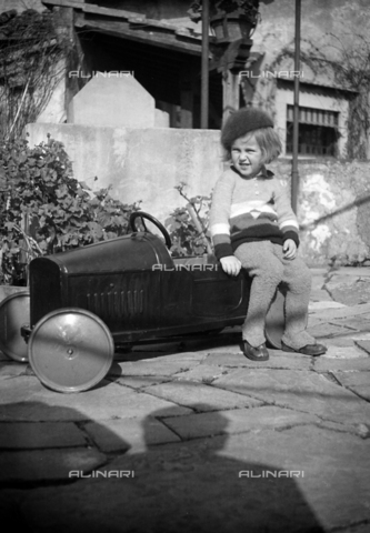 CAD-S-290048-0001 - Child portrait sitting on a toy car - Date of photography: 1920-1930 ca - Fratelli Alinari Museum Collections-Cammarata Donation, Florence