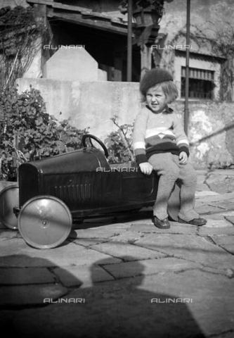 CAD-S-290048-0001 - Ritratto di bambino seduto su un'automobile giocattolo - Data dello scatto: 1920-1930 ca - Raccolte Museali Fratelli Alinari (RMFA)-donazione Cammarata, Firenze