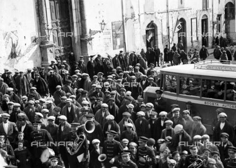 """CAD-S-420006-0009 - Musical band and crowd at Piana dei Greci (today Piana degli Albanesi). On the left the portal of the church of Santa Maria Odigitria. On the right a coach with the word """"Sciacca"""" - Data dello scatto: 09-15/11/1929 - Archivi Alinari, Firenze"""