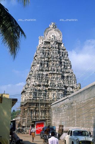 CAL-F-006617-0000 - Veduta del tempio Kamakshi Amman, a Kanchipuram, nei pressi di Mahabalipuram, in India. La città è situata lungo la direttrice meridionale del Gange. L'edificio, appartenente alla cultura Tamilnad, è dedicato alla dea Parvati; al piano terra sono visibili delle persone, un automobile ed un cartello pubblicitario della COCA COLA. - Data dello scatto: 1989 - 1991 - Archivi Alinari, Firenze