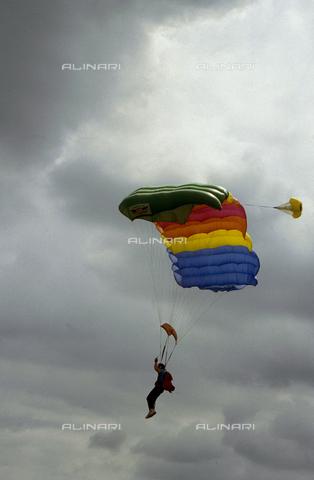 CAL-F-006990-0000 - Paracadutista ripreso durante un lancio. Sullo sfondo un cielo solcato da nuvole