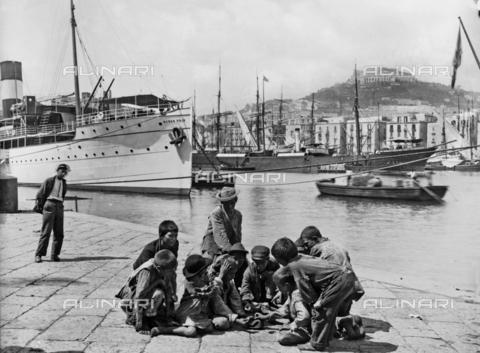 CGA-F-005404-0000 - Bambini giocano alla morra sul molo del porto di Napoli - Data dello scatto: 1890-1900 ca. - Archivi Alinari, Firenze
