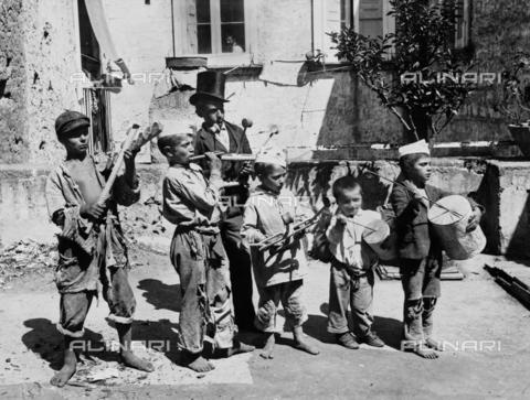 """CGA-F-005405-0000 - Children with musical instruments (music players and """"guaglioni"""") in a street of Piedigrotta, Naples - Data dello scatto: 1890 ca. - Archivi Alinari, Firenze"""