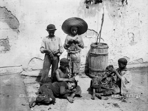 """CGA-F-005408-0000 - Children taking off lice from each other head in a street of Naples, in the past they were called """"Pedocchiosi o Paladini del Porto"""" - Data dello scatto: 1890 ca. - Archivi Alinari, Firenze"""