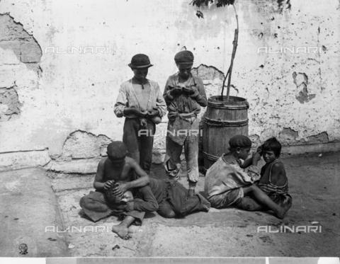 """CGA-F-05408A-0000 - Bambini che si spidocchiano, in passato chiamati """"Pedocchiosi o Paladini del Porto"""",  in una strada di Napoli - Data dello scatto: 1890-1900 ca. - Archivi Alinari, Firenze"""